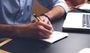 Ein Mann der neben seinem Laptop etwas auf einem Zettel notiert
